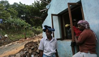 Sri Lankan men stand by their damaged house caused by mudslide at the Koslanda tea plantation in Badulla district, about 220 kilometers (140 miles) east of Colombo, Wednesday, Oct. 29, 2014. (AP Photo/Eranga Jayawardena)