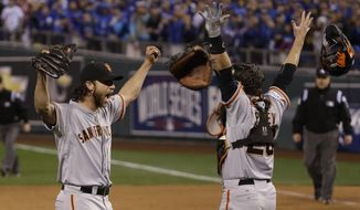 San Francisco Giants pitcher Madison Bumgarner, left, and Buster Posey celebrate after winning 3-2 to win the series over Kansas City Royals after Game 7 of baseball's World Series Wednesday, Oct. 29, 2014, in Kansas City, Mo. (AP Photo/Matt Slocum)