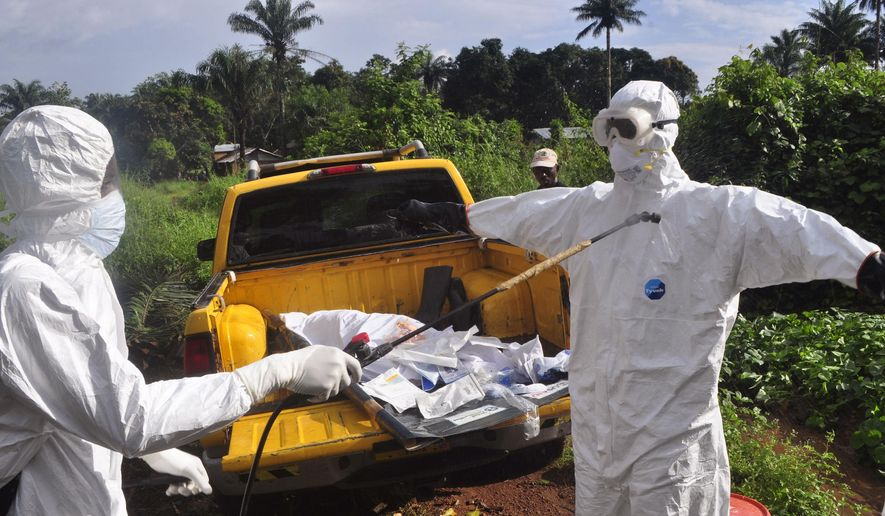 A health worker sprays disinfectant onto a college after they worked with the body of a man, suspected of contracting and dying form the Ebola virus on the outskirts of Monrovia, Liberia, Monday, Oct. 27, 2014. (AP Photo/Abbas Dulleh) ** FILE **