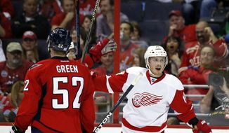 Detroit Red Wings center Gustav Nyquist (14), from Sweden, celebrates his goal as Washington Capitals defenseman Mike Green (52) watches, in the second period of an NHL hockey game, Wednesday, Oct. 29, 2014, in Washington. (AP Photo/Alex Brandon)