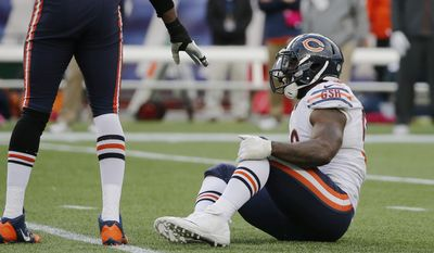 Chicago Bears defensive end Lamarr Houston, seated, holds his knee after injuring it while celebrating a sack on New England Patriots backup quarterback Jimmy Garoppolo with about 3 minutes left in an NFL football game on Sunday, Oct. 26, 2014, in Foxborough, Mass. The Patriots won 51-23.  (AP Photo/Elise Amendola)