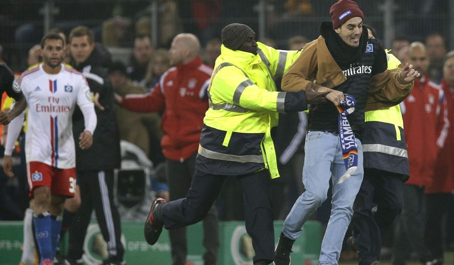 Members of the security staff of Hamburg catch a young man who runs onto the pitch during the German soccer cup second round match between Hamburger SV and FC Bayern Munich at the Imtech Arena Stadium in Hamburg, Germany, Wednesday, Oct. 29, 2014. (AP Photo/Michael Sohn)