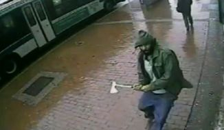 FILE- In this Oct. 23, 2014 image taken from surveillance video provided by the New York City Police Department, Zale Thompson approaches New York City police officers with a hatchet, in the Queens borough of New York. Although NYC Police Commissioner William Bratton called it an act of terrorism, characterizing as such has raised questions about what qualifies as terrorism in an era more than 13 years removed from the Sept. 11 attacks. (AP Photo/New York Police Department, File)