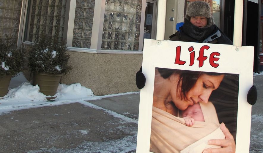 FILE - In this Feb. 20, 2013 file photo, an abortion protester stands outside the Red River Valley Women's Clinic in downtown Fargo, N.D. The director of North Dakota's sole abortion provider says medical abortions have ceased at the Fargo clinic following a North Dakota Supreme Court ruling Tuesday, Oct. 28, 2014, that upheld a 2011 state law limiting the use of drugs to perform abortions. (AP Photo/Dave Kolpack, File)