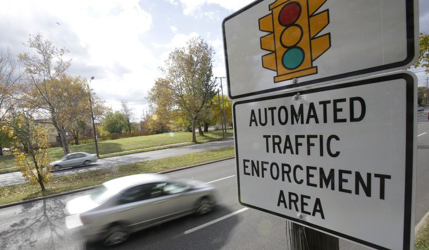 Motorists drive past a sign warning of upcoming traffic cameras  Wednesday, Oct. 29, 2014, in Cleveland. Cleveland Mayor Frank Jackson and others are making a last-minute pitch to defeat a ballot measure that would severely limit use of automated speed and red light cameras. Approval of a measure on Tuesday's ballot in Cleveland would require police officers to write tickets at automated camera sites. (AP Photo/Tony Dejak)