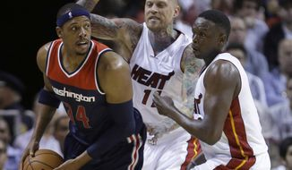 Washington Wizards forward Paul Pierce (34) looks for an open teammate past Miami Heat forward Chris Andersen (11) and forward Luol Deng of Sudan, right, during the first half of an NBA basketball game, Wednesday, Oct. 29, 2014 in Miami. (AP Photo/Wilfredo Lee)