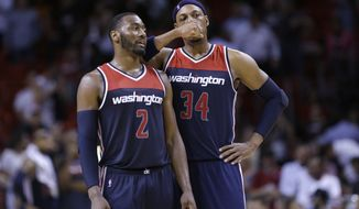 Washington Wizards guard John Wall (2) and forward Paul Pierce (34) talk during final minutes of the second half of an NBA basketball game against the Miami Heat, Wednesday, Oct. 29, 2014 in Miami. The Heat defeated the Wizards 107-95. (AP Photo/Wilfredo Lee)