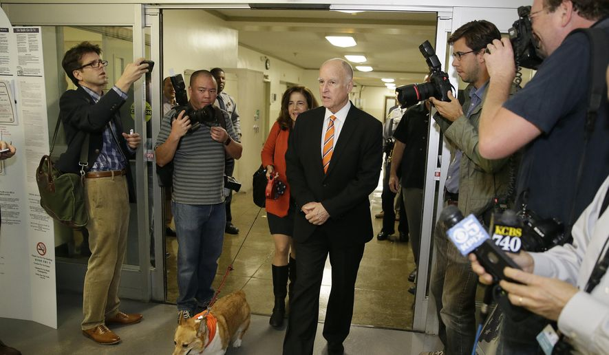 California Gov. Jerry Brown walks with his wife Anne Gust and his dog, Sutter, to vote at the Alameda County Registrar of Voters office Thursday, Oct. 30, 2014, in Oakland, Calif. Brown is facing Republican challenger Neel Kashkari in the Nov. 4 election. (AP Photo/Eric Risberg)