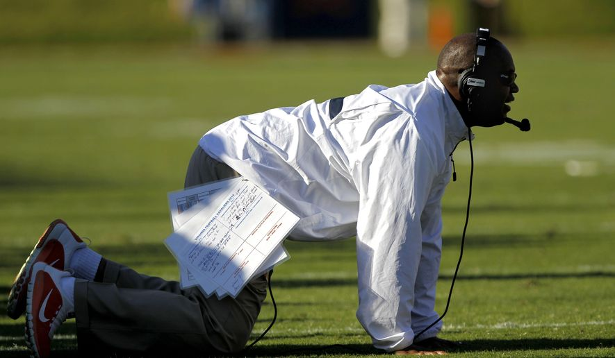 Virginia head coach Mike London falls to his knees after a substitution penalty during the fourth quarter of an NCAA football game against North Carolina in Charlottesville, Va., Saturday, Oct. 25, 2014. (AP Photo/The Daily Progress, Ryan M. Kelly)