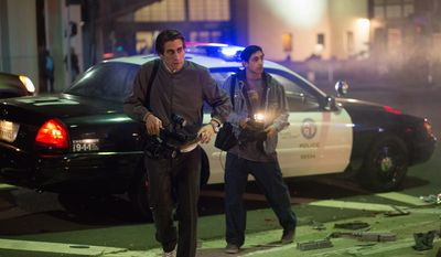 "Jake Gyllenhaal, left, and Riz Ahmed appear in a scene from the film, ""Nightcrawler."" This nervy and often gripping movie is about evil voyeurism and local news, which in ""Nightcrawler's"" bleak satirical universe are the same thing. (Open Road Films via Associated Press)"