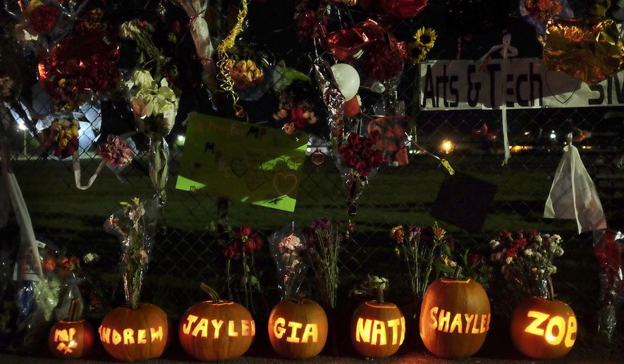 In this photo taken on Oct. 28, 2014, pumpkins with the names of the victims and shooter of the Marysville-Pilchuck High School shooting carved into them sit along the south fence of the school in Marysville, Wash., which has become a growing memorial. Jaylen Fryberg fatally shot two students and gravely wounded three others before killing himself.  (AP Photo/The Herald, Genna Martin)