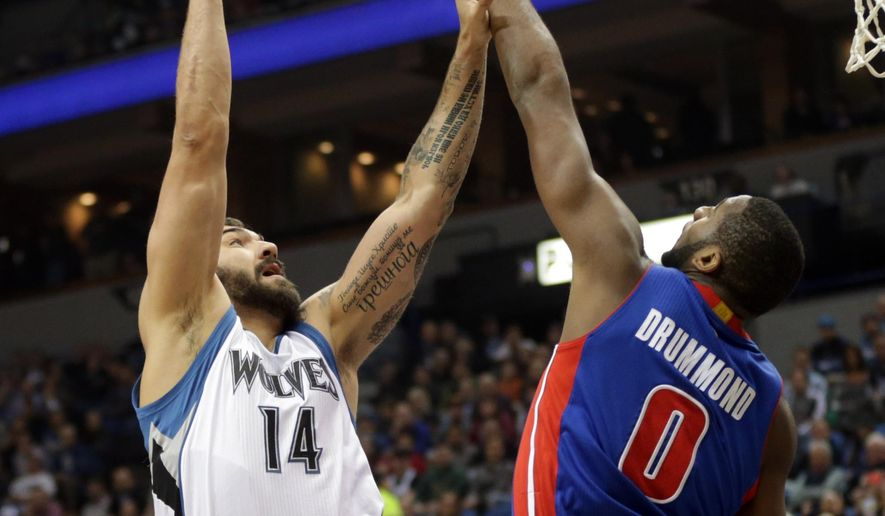 Minnesota Timberwolves' Nikola Pekovic, left, of Montenegro, shoots over Detroit Pistons' Andre Drummond in the first quarter of an NBA basketball game, Thursday, Oct. 30, 2014, in Minneapolis. (AP Photo/Jim Mone)