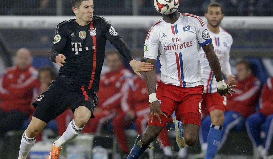 Bayern's Robert Lewandowski from Poland, left, and Hamburg's Johan Djourou from Switzerland, right, challenge for the ball during the German soccer cup second round match between Hamburger SV and FC Bayern Munich at the Imtech Arena Stadium in Hamburg, Germany, Wednesday, Oct. 29, 2014. (AP Photo/Michael Sohn)