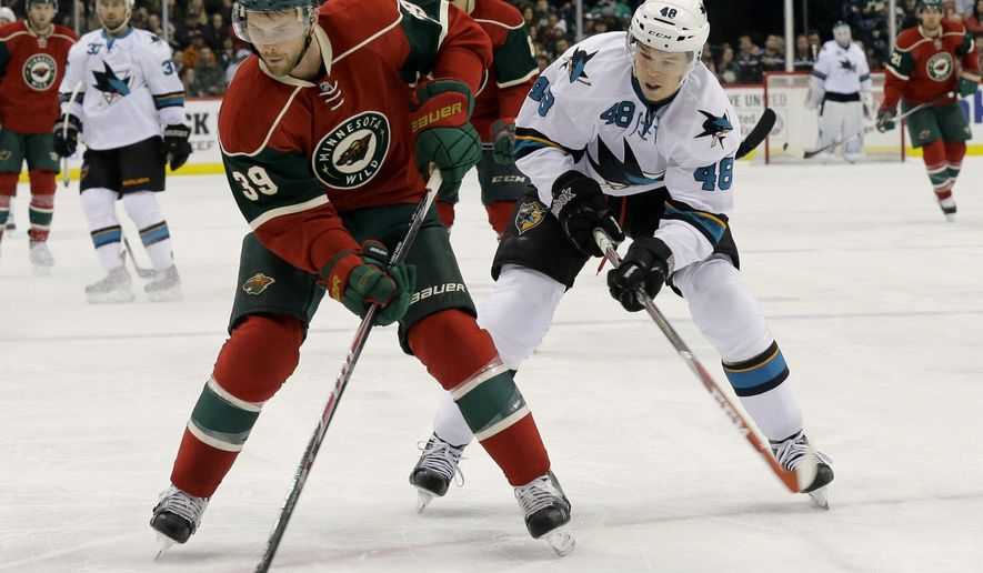 Minnesota Wild defenseman Nate Prosser (39) and San Jose Sharks center Tomas Hertl (48), of the Czech Republic, chase the puck during the second period of an NHL hockey game in St. Paul, Minn., Thursday, Oct. 30, 2014. (AP Photo/Ann Heisenfelt)