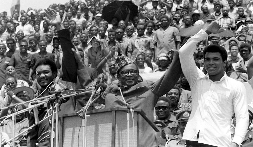 FILE - This is a  Sept. 22, 1974 file photo of Zaire's President Mobutu Sese Seko, center, as he raises the arms of heavyweight champ George Foreman, left, and Muhammad Ali, right, in Kinshasa,  Zaire. It was 40 years ago that two men met just before dawn on Oct. 30, 1974, to earn $5 million in the Rumble in the Jungle. In one of boxing's most memorable moments, Muhammad Ali stopped the fearsome George Foreman to recapture the heavyweight title in the impoverished African nation of Zaire. (AP Photo/Horst Faas, File)