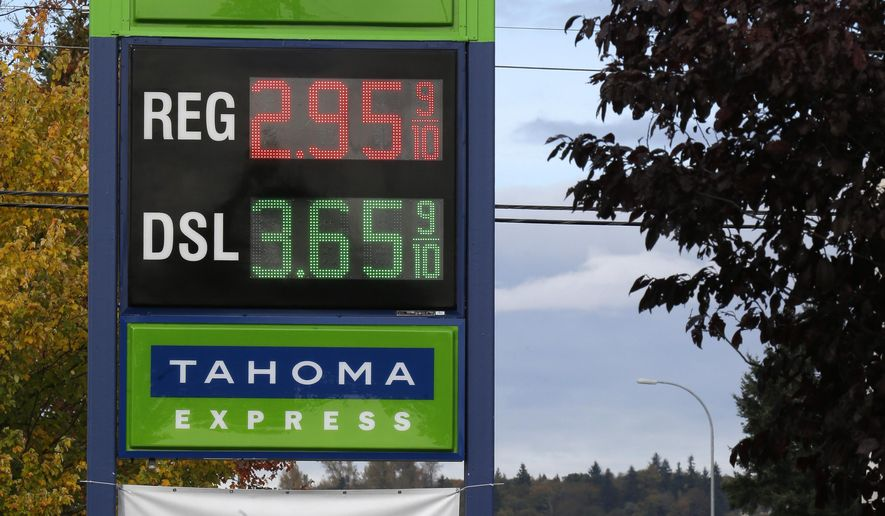 As cars wait in traffic at right, a sign at a gas station advertises regular unleaded gasoline for $2.95 a gallon Wednesday, Oct. 29, 2014 in Fife, Wash. The Tahoma Market station is one of only a few stations in the Seattle-Tacoma area that are selling gas at the current national average of below $3 a gallon. (AP Photo/Ted S. Warren)