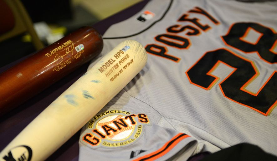 Bats from Salvador Perez of the Kansas City Royals and Hunter Pence of the  San Francisco Giants are displayed with a champagne drenched World Series jersey from Buster Posey of the of the Giants during a display of World Series artifacts which were being delivered to the Baseball Hall of Fame and Museum in Cooperstown Thursday, Oct. 30, 2014, at Albany International Airport in Colonie, N.Y.   (AP Photo/The Albany Times Union, Will Waldron)  TROY, SCHENECTADY; SARATOGA SPRINGS; ALBANY OUT