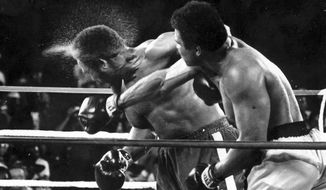 Perspiration flies from the head of George Foreman as he takes a right from challenger Muhammad Ali in the seventh round in the match dubbed Rumble in the Jungle in Kinshasa, Zaire. Ali knocked out Foreman in the eighth round. (AP Photo/Ed Kolenovsky, File)