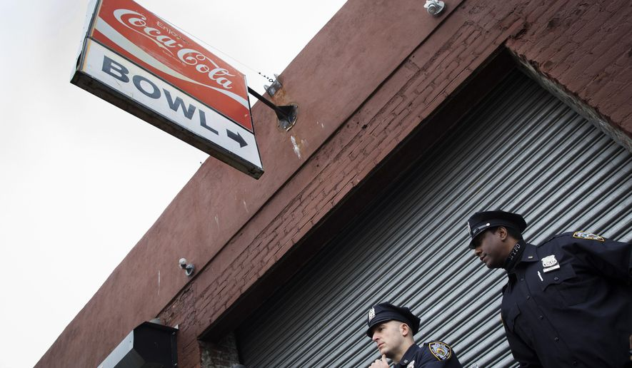 FILE - In this Oct. 24, 2014, file photo, police officers stand outside The Gutter bowling alley after it was closed when it was discovered it had been visited by Craig Spencer, a Doctors Without Borders physician who tested positive for the Ebola virus, in the Williamsburg neighborhood of the Brooklyn borough of New York. After Spencer was settled at a hospital, New York department of health workers reconstructed in detail his movements in the days since his  return form Guinea where he was treating patients with Ebola. They combined information from his Metrocard, phone records and friends to paint a picture of his days and to assess whether anyone else may have been exposed and found that he had visited the bowling alley. (AP Photo/John Minchillo, File)