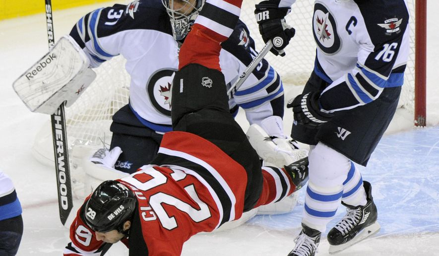 New Jersey Devils' Ryane Clowe (29) is upended by Winnipeg Jets' Andrew Ladd, right, as Jets goaltender Ondrej Pavelec, of the Czech Republic, looks on during the second period of an NHL hockey game Thursday, Oct. 30, 2014, in Newark, N.J. (AP Photo/Bill Kostroun)