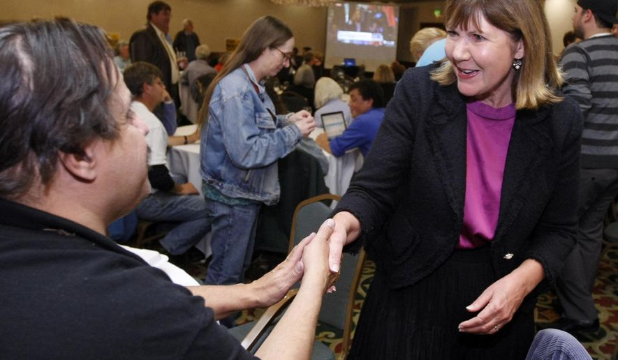 FILE - In this Nov. 6, 2012 file photo, then-Congressional District 1 candidate Ann Kirkpatrick, D-Arizona, greets campaign supporter Tom Morello during an election night party in Flagstaff, Ariz. The Democratic party is trying hard to hang on to the seat held by Kirkpatrick and needs Navajo voters who lean Democrat to turn out in droves in what is one of the hardest-fought congressional races in the country. Kirkpatrick has learned to speak the Navajo language, regularly appears at the tribe's legislative sessions and has sponsored fairs and rodeos. Her Republican opponent, Arizona House Speaker Andy Tobin, has been to the Navajo Nation several times, including speaking at a Navajo Code Talkers event at the tribal capital. (AP Photo/Ralph Freso, File)