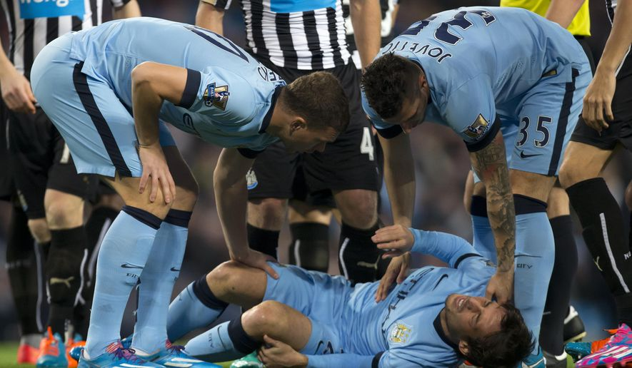 Manchester City's Edin Dzeko, left, and Stevan Jovetic stand over an injured David Silva during the English League Cup soccer match between Manchester City and Newcastle at the Etihad Stadium, Manchester, England, Wednesday Oct. 29, 2014. (AP Photo/Jon Super)