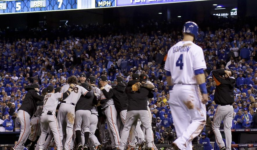 The San Francisco Giants celebrate after Game 7 of baseball's World Series as Kansas City Royals' Alex Gordon walks off, Wednesday, Oct. 29, 2014, in Kansas City, Mo. The Giants won 3-2 to win the series. (AP Photo/Matt Slocum)