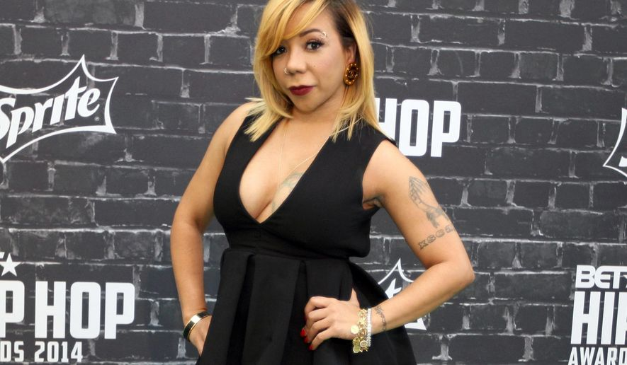 "FILE - In this Sept. 20, 2014 file photo, TV personality Takema ""Tiny"" Harris arrives at the 2014 BET Hip Hop Awards in Atlanta. Harris, the wife of rapper T.I., has the attention of skeptical eye doctors and social media haters over a procedure she underwent to permanently lighten the color of her eyes. Harris, once a member of the '90s R&B group Xscape, told ABC News on Thursday that she traveled to Africa a little more than two weeks ago for cosmetic eye implants that changed her eye color from brown to ice gray.  (Photo by Dan Harr/Invision/AP, File)"