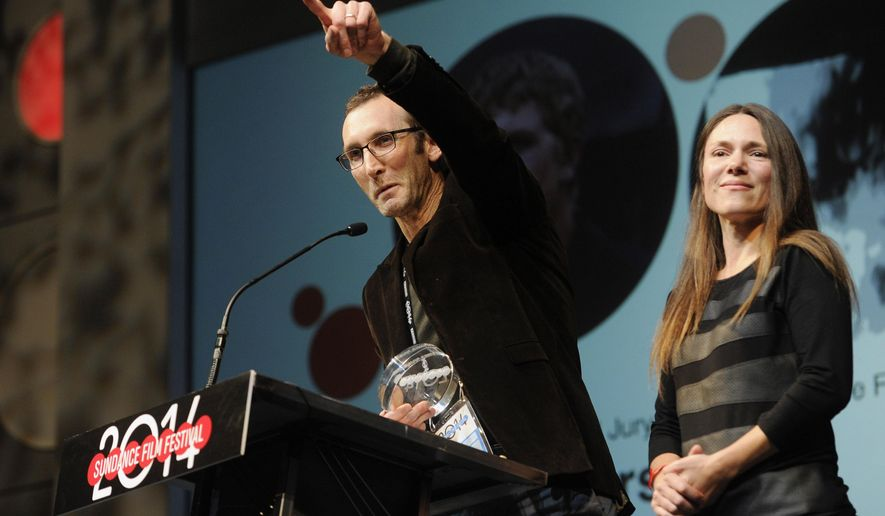 "FILE - In this Jan. 25, 2014 file photo, Jesse Moss, director of ""The Overnighters,"" accepts the U.S. Documentary Special Jury Award for Intuitive Filmmaking alongside his wife Amanda, a producer on the film, during the 2014 Sundance Film Festival Awards Ceremony in Park City, Utah. Residents in Williston, N.D., will get to view a a screening of the award-winning documentary about the gritty side of life in the oil boomtown Thursday, Oct. 30, 2014. (Photo by Chris Pizzello/Invision/AP)"