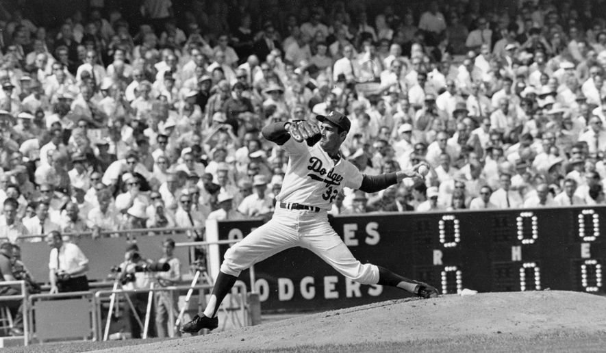 FILE - In this Oct. 6, 1966 file photo, Los Angeles Dodgers' Sandy Koufax, pitches against the Baltimore Orioles in game two of the World Series baseball game in Los Angeles.In 1965, Koufax didn't pitch the Dodgers' Series opener at Minnesota because of Yom Kippur and lost to Jim Kaat the following day. Koufax pitched a four-hit shutout on three days' rest to win Game 5, then came back with a three-hit shutout on two days' rest to win Game 7. (AP Photo/File)