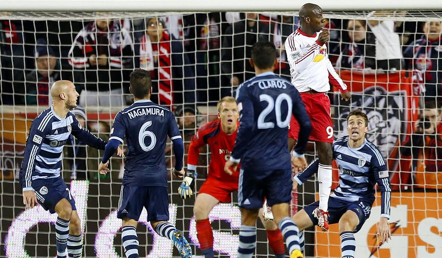 New York Red Bulls forward Bradley Wright-Phillips (99) heads a cornerkick in for a goal for the winning score against Sporting Kansas City in an MLS playoff soccer match at Red Bull Arena in Harrison, N.J., Thursday, Oct. 30, 2014. The Red Bulls defeated Kansas City 2-1. (AP Photo/Rich Schultz)
