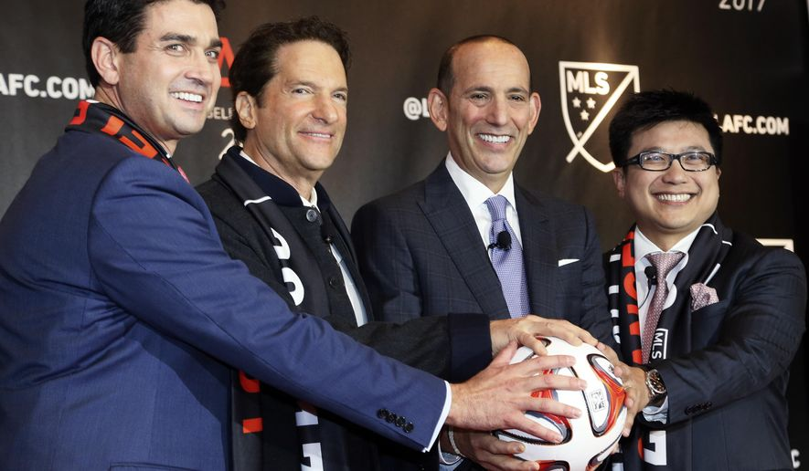 Major League Soccer announces the details of the league's plan to launch a second team in the Los Angeles area after shutting down Chivas USA, at a news conference in Los Angeles Thursday, Oct. 30, 2014. Flanking MLS commissioner Don Garber, second from right, are members of the ownership group Tom Penn, Peter Guber and Henry Nguyen, right. The new team, the Los Angeles Football Club, will begin play in 2017 with strong owners and plans for a soccer-specific stadium. (AP Photo/Nick Ut)
