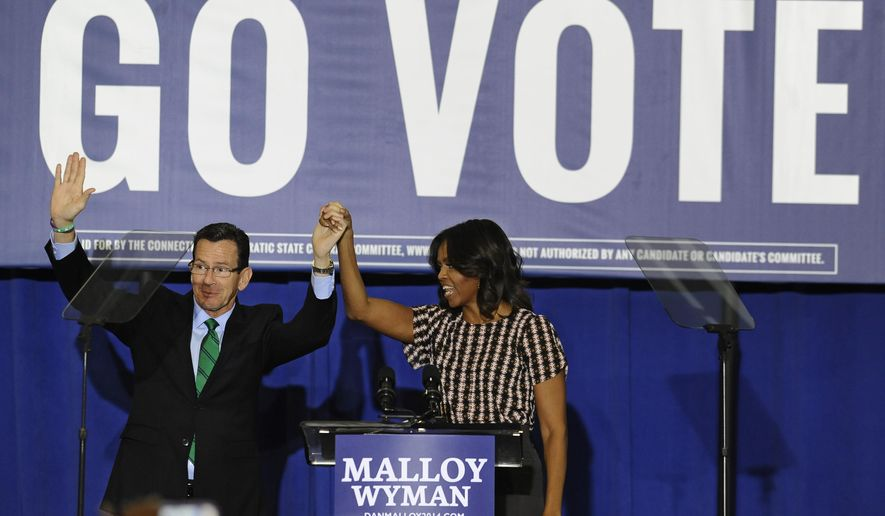 First lady Michelle Obama, right, holds hand with Connecticut Gov. Dannel P. Malloy, during a rally to support Malloy, Thursday, Oct. 30, 2014, in New Haven, Conn. (AP Photo/Jessica Hill)