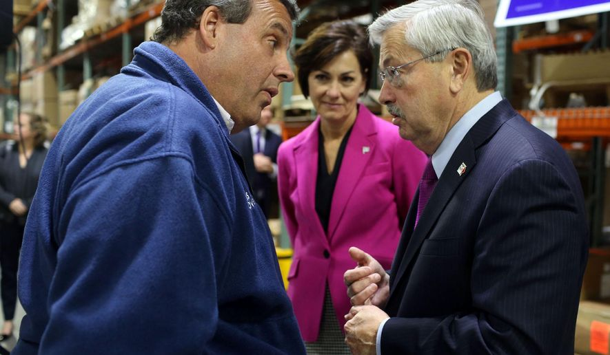 New Jersey Gov. Chris Christie, talks with Iowa Gov. Terry Branstad, as Iowa Lt. Gov. Kim Reynolds, center, looks on, after speaking at a get-out-the-vote rally, Thursday, Oct. 30, 2014 at the Winegard Company in Burlington, Iowa. (AP Photo/The Hawk Eye, John Lovretta)