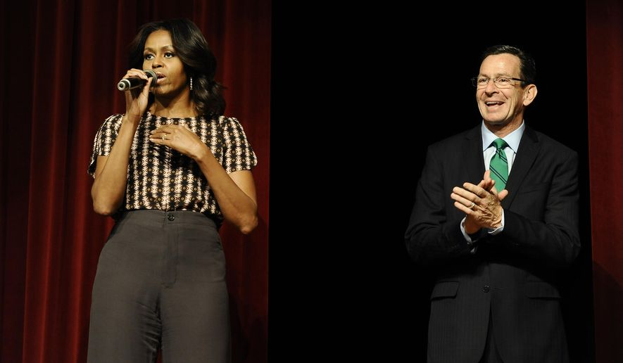 First Lady Michelle Obama, left, speaks as Connecticut Gov. Dannel P. Malloy listens after surprising a group of supporters in an overflow room to a rally, Thursday, Oct. 30, 2014, in New Haven, Conn. (AP Photo/Jessica Hill)