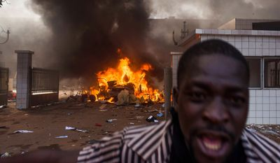 A car burns outside the parliament building in Burkina Faso as people protest against their longtime President Blaise Compaore who is seeking another term in Ouagadougou, Burkina Faso, Thursday, Oct. 30, 2014. (AP Photo/Theo Renaut)