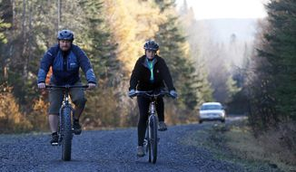Nurse Kaci Hickox, right, and her boyfriend, Ted Wilbur are followed by a Maine State Trooper as they ride bikes on a trail near her home in Fort Kent, Maine, Thursday, Oct. 30, 2014.  The couple went on an hour-long ride.  State officials are going to court to keep Ms. Hickox in quarantine for the remainder of the 21-day incubation period for Ebola that ends on Nov. 10. Police are monitoring her, but can't detain her without a court order signed by a judge. (AP Photo/Robert F. Bukaty)