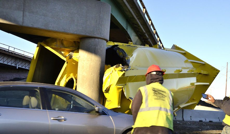 In this Tuesday, Oct. 28, 2014 photo, a sand silo being carried on a tractor-trailer is wedged under the bottom of an overpass with a 15-foot clearance at the Port Neal Interchange on Interstate 29 near Salix, Iowa. Officials are hoping that work to raise overpasses on Interstate 29 will reduce frequent crashes by vehicles hauling tall loads. (AP Photo/The Sioux City Journal, Tim Hynds)