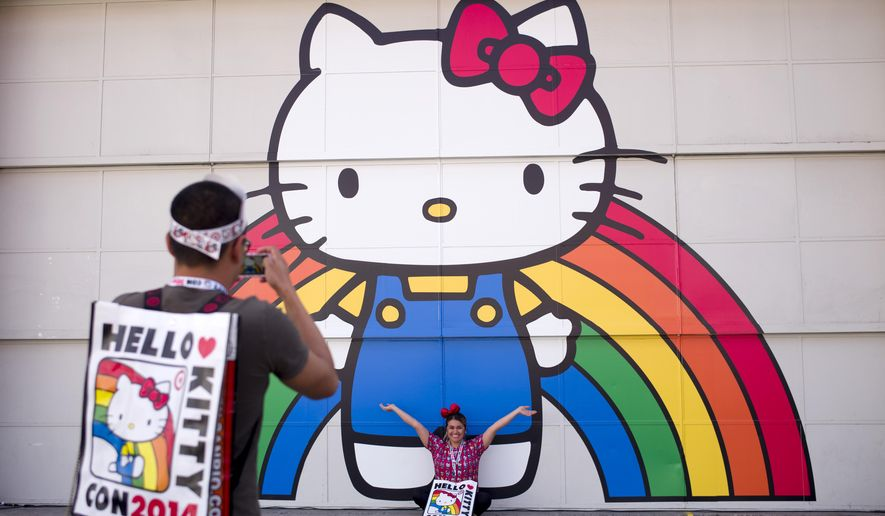 Keith Nunez, left, takes pictures of his wife, Carolina, at the first-ever Hello Kitty fan convention,  Hello Kitty Con, held at the Geffen Contemporary at MOCA, Thursday, Oct. 30, 2014, in Los Angeles. The convention was held to honor the character's 40th birthday. (AP Photo/Jae C. Hong)