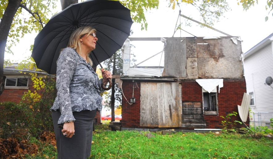 Kathy Angerer, director of community and economic development for the city of Hamtramck, Mich., stands near one of the city owned homes on Yemens Street in Hamtramck, Mich. on Tuesday Oct. 28, 2014. Hamtramck and Highland Park are undertaking comprehensive attempts to count blighted properties within their boundaries as efforts ramp up in cities around the state to deal with vacant and dilapidated buildings. (AP Photo/Detroit News, Max Ortiz)  DETROIT FREE PRESS OUT; HUFFINGTON POST OUT  (Max Ortiz/The Detroit News)2014