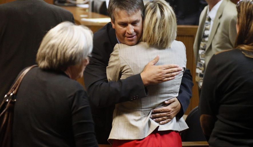 Republican Rep. Barry Moore hugs his wife Heather Moore after he was cleared of all charges in his trial, Thursday, Oct. 30, 2014, in Opelika, Ala. A jury found Moore not guilty of charges of perjury and giving false information on Thursday in the first trial to come out of an investigation that targeted Alabama House Speaker Mike Hubbard.  (AP Photo/Opelika-Auburn News, Todd J. Van Emst)