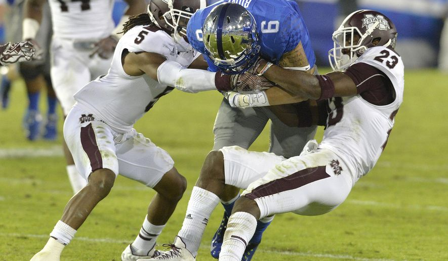 Kentucky's Blake Bone, center, is wrapped up by Mississippi State's Jamerson Love, left, and Taveze Calhoun during the fourth quarter of an NCAA college football game at Commonwealth Stadium in Lexington, Ky., Saturday, Oct. 25, 2014. Mississippi State won 45-31. (AP Photo/Timothy D. Easley)