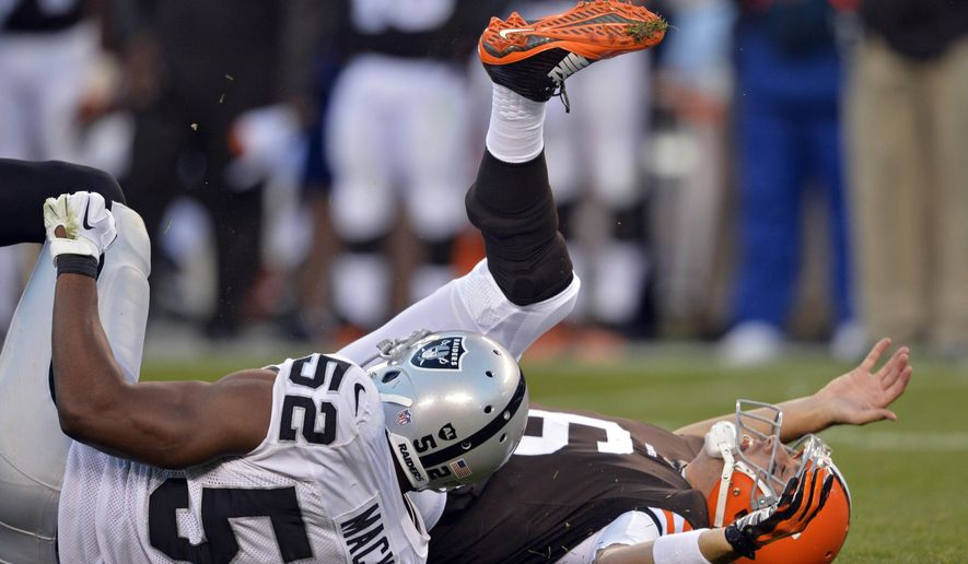 Cleveland Browns quarterback Brian Hoyer is hit by Oakland Raiders linebacker Khalil Mack (52) after throwing an incomplete pass in the third quarter of an NFL football game, Sunday, Oct. 26, 2014, in Cleveland. (AP Photo/David Richard)