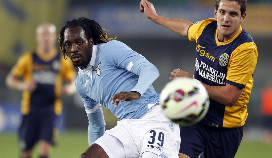 Lazio's Luis Cavanda, left, and Hellas Verona's Juanito vie for the ball during a Serie A soccer match at Bentegodi stadium in Verona, Italy, Thursday, Oct. 30, 2014. (AP Photo/Felice Calabro')