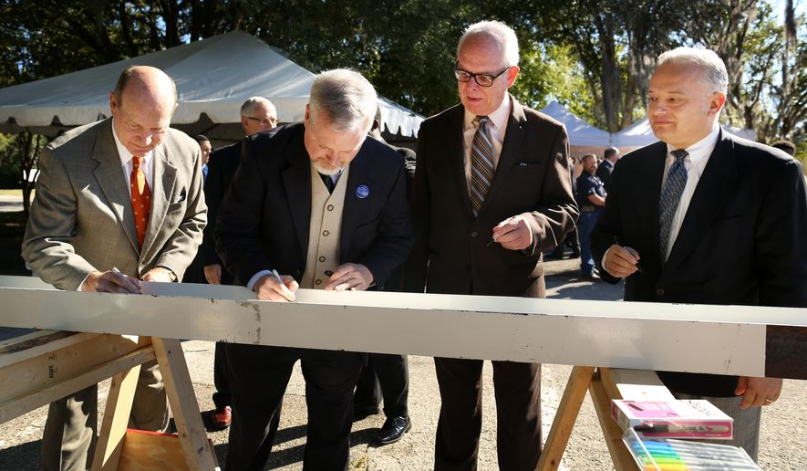 Dave Kratzer, University of Florida vice president of student affairs, from left, Ed Braddy, Gainesville mayor, Bernie Machen, UF president and Tony Manna, chairman of Signet Enterprises participate in a beam signing during a groundbreaking ceremony for UF's Infinity Hall Thursday, Oct. 23, 2014. (AP Photo/The Gainsville Sun, Doug Finger)