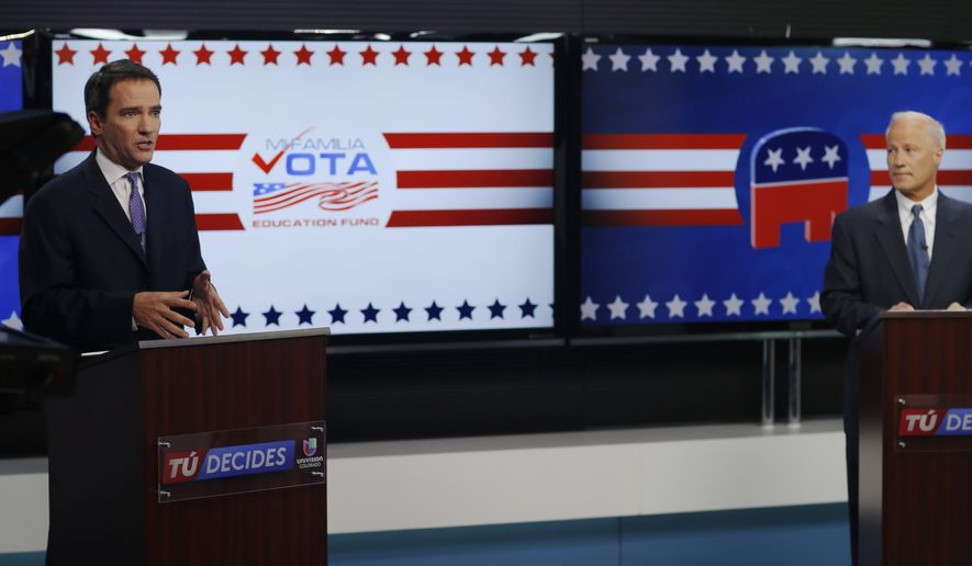 Incumbent U.S. Rep. Mike Coffman, R-Colo., right, looks on as his Democratic challenger, Andrew Romanoff, makes point as they debate in Spanish in the studio of a television station in Denver on Thursday, Oct. 30, 2014. (AP Photo/David Zalubowski)