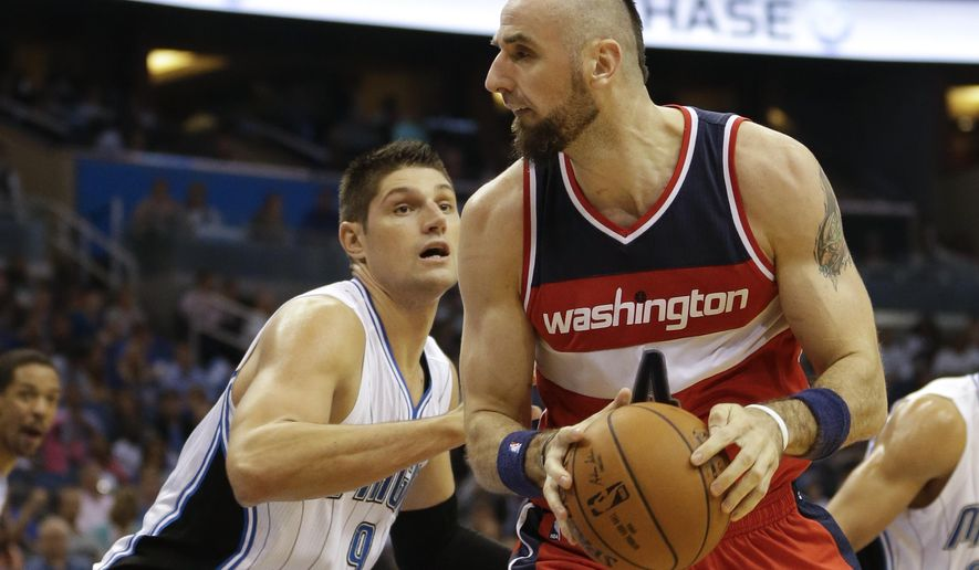 Washington Wizards center Marcin Gortat, right, looks for a way around Orlando Magic's Nikola Vucevic (9) during the first half of an NBA basketball game in Orlando, Fla., Thursday, Oct. 30, 2014. (AP Photo/John Raoux)