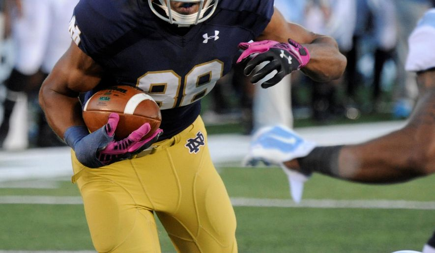 In this Oct. 11, 2014 photo, Notre Dame wide receiver Corey Robinson makes a catch during action in an NCAA college football game against North Carolina in South Bend, Ind. Irish coaches say Robinson's cool demeanor and ability to learn is helping him to grow into a big-play receiver.  (AP Photo/Joe Raymond)