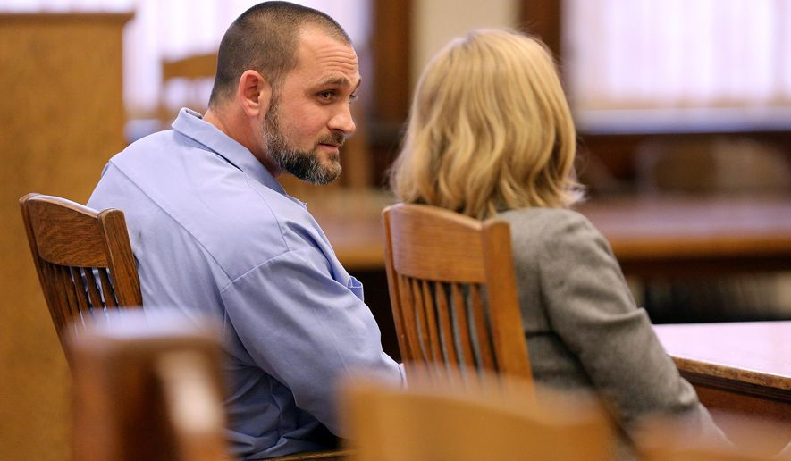 In this photo taken on Wednesday, Oct. 29, 2014, convicted killer Sean Rhomberg talks to his attorney during his resentencing hearing at the Dubuque County Courthouse in Dubuque, Iowa.  Rhomberg was given life without parole in 1992 for stabbing a 70-year-old woman to death when he was 16.  Judge Tom Bitter resentenced him to life, but left it up to the parole board to determine if he will be granted parole. Rhomberg's attorney filed a motion for a resentencing after the Iowa Supreme Court ruled that a U.S. Supreme Court decision that banned sentences of life without parole for juveniles can be applied retroactively. (AP Photo/The Telegraph Herald, Dave Kettering)  MAGS OUT, TV OUT, MANDATORY CREDIT