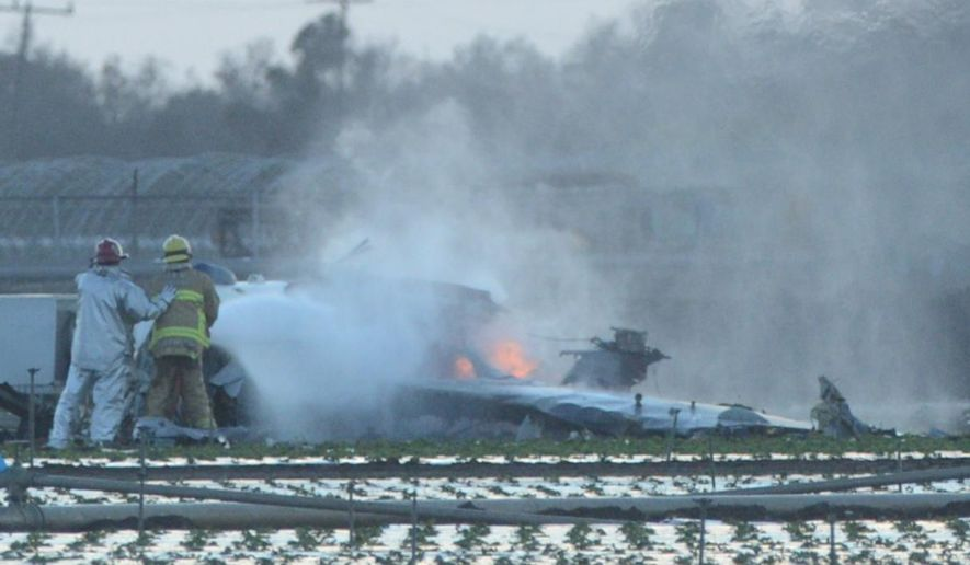 Firefighters extinguish the remaining flames of a military airplane that crashed in a field near Naval Station Ventura County near Port Hueneme, Calif., killing the pilot Wednesday, Oct. 29, 2014. The plane crashed and disintegrated at around 5:15 p.m. (AP Photo/The Ventura County Star,  Karen Quincy Loberg) LOS ANGELES TIMES OUT, LOS ANGELES DAILY NEWS OUT